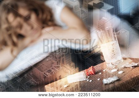 Way to deal with depression. Close up of pills on the table while depressed young woman lying in the background