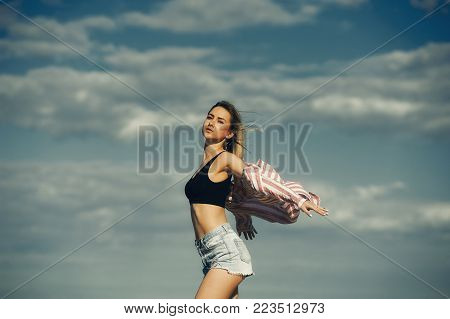 Happy young girl standing with outstretched arms against the sky , a young woman breathing fresh air.