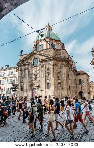Prague,  Czech Republic - August 18, 2017: Crowd of tourists crossing road near Charles Bridge against St. Francis Of Assissi Church in historic centre of Prague