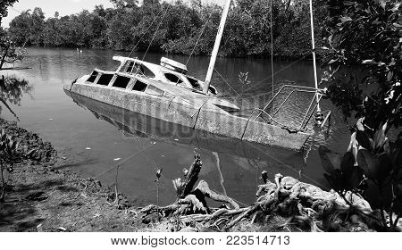 Derelict partially sunken weathered hull of a white motor yacht in a creek listing to the side