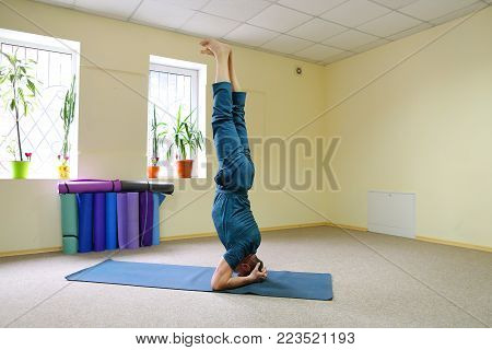 Young brunette of American origin sits on yoga mat and performs longitudinal twine. Short-haired sportswoman dressed in blue sports pants and blue t-shirt. Room light and spacious, under wall multi-colored yoga mats. Concept of to maintain body in good