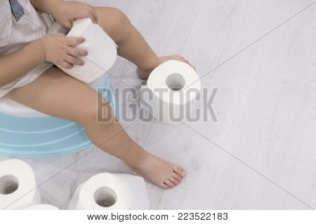 smiling baby sitting on chamber pot with toilet paper rolls