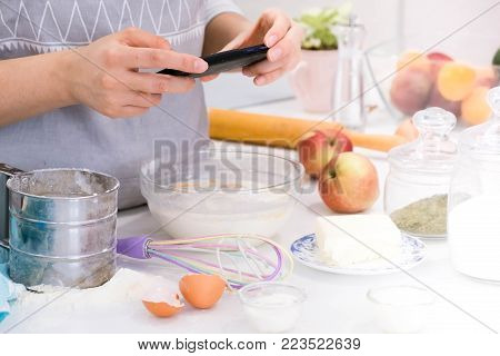 Cooking blogger is cooking at the kitchen in sunny day and is making photo at smartphone of cooking process. Young pretty woman cooking at kitchen with happy emotions