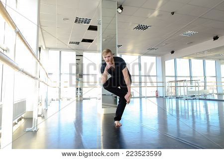Male sportsman preparing body for loads and doing stretching. Blonde boy wears black suit and sitting on floor near mirrors. Concept of doing warm up and training for being in good shape.