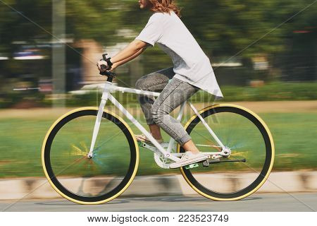 Cropped image of cycling young woman, blurred motion