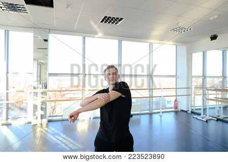 Ballroom dancer warm up before training, fair-haired tattooed guy wearing comfortable black sport clothes. Male wag legs in gym with big windows and mirrors. Concept of choreographic school, hall for group or individual workouts, sportswear