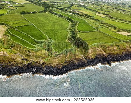 Aerial view of fields cliff and the Atlantic ocean near the small village of Ginetes on Sao Miguel Island in Portugal.