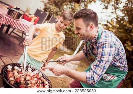 Leisure,food,people and holidays concept-man cooking meat on barbecue grill for his family at summer outdoor party