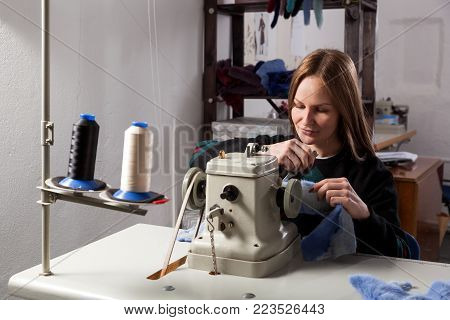 Sewing process of the female fur coat. A young cheerful woman furrier smiles and sews a bright fur coat of natural blue fur
