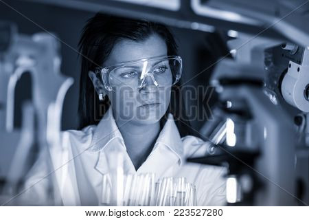 Scientists researching in scientific laboratory. Young female young PhD student scientist researching in the life science research laboratory. Biochemistry, genetics, forensics, microbiology ..