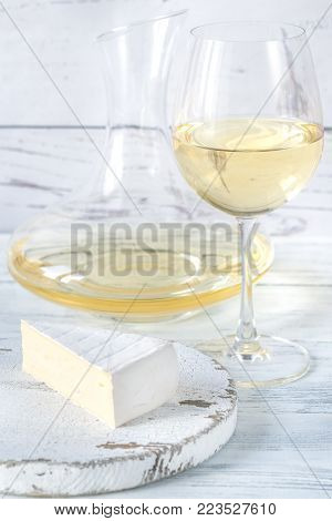 Glass of white wine with piece of cheese