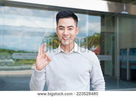 Handsome asian man  showing ok hand sign outdoors