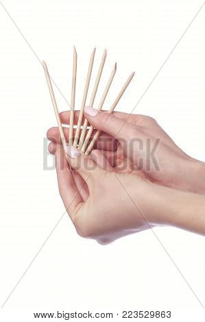 Manicurist doing cleaning cuticle on the female fingers with cosmetic stick