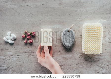 cropped view of hand with stones, dried roses, natural soap, pumice and bath sponge for spa on marble surface