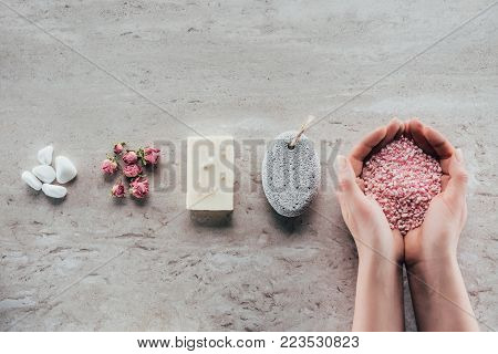cropped view of hands with sea salt on marble surface with stones, dried roses, natural soap and pumice for spa