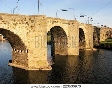 Old arched bridge over the River Aude at Carcassonne, France, catching afternoon sunlight