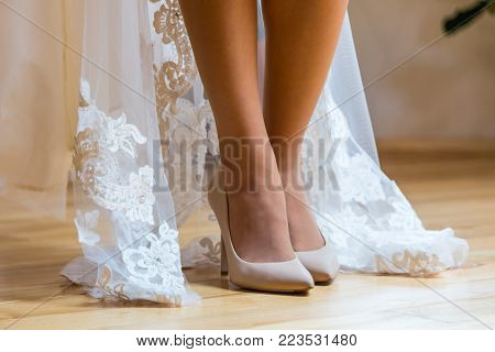 Sexual legs of the bride. The bride is standing on a wooden floor, shoe in cream shoes, and she shows her beautiful legs.