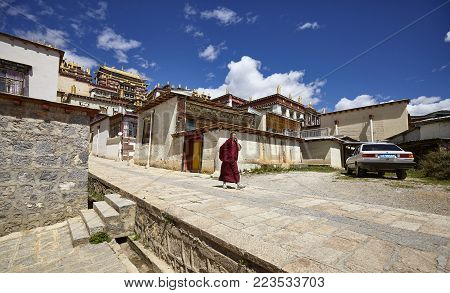 Shangri-La, China - September 25, 2017: Monk walks down the road in Songzanlin Monastery, built in 1679, is the largest Tibetan Buddhist monastery in Yunnan province, known as Little Potala Palace.