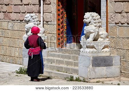 Shangri-La, China - September 25, 2017: Woman in front of a temple in Songzanlin Monastery, built in 1679, is the largest Tibetan Buddhist monastery in Yunnan province, known as Little Potala Palace.