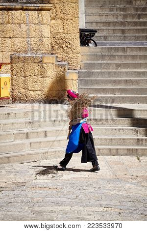 Shangri-La, China - September 25, 2017: Woman with a broom in the Songzanlin Monastery, built in 1679, is the largest Tibetan Buddhist monastery in Yunnan province, known as Little Potala Palace.