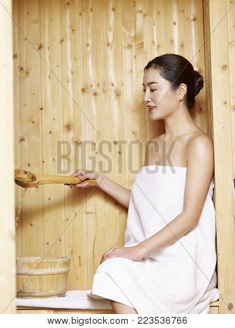 beautiful young asian woman wrapped in white towel sitting in sauna.
