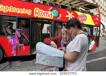 Rome, Italy - APRIl 7, 2017 : Two tourists looking map of Rome. In the background tourist bus with passengers on street in Rome, Italy.
