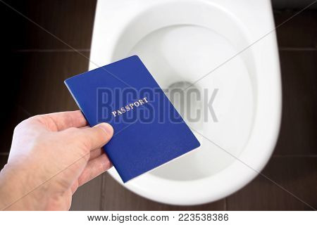 Hand holds the citizen's passport over the toilet, throw out his passport. Concept - change of citizenship, loss of passport, political problems, infringement of rights