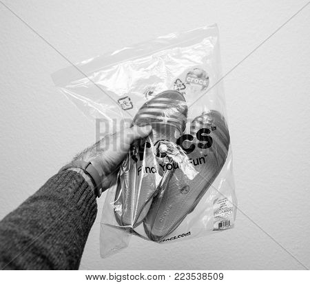 PARIS, FRANCE - JAN 23, 2018: Man holding a pair of new female shoes by Crocs Isabella Sandal bought online - plastic back new packaging