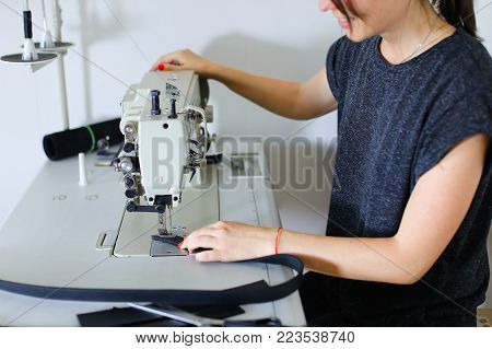 Seamstress sewing belt using sewing machine. Girl working at factory, female with red nails and bracelet sitting near table in workshop stitching black leather strap using special mechanism. Concept of leather industry, accessories manufacturing or crafts