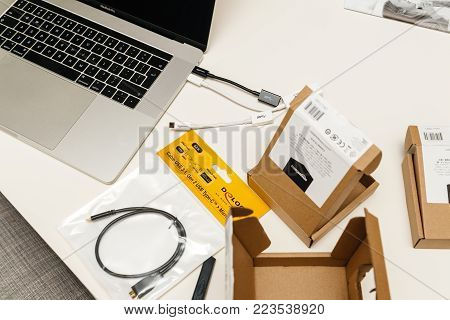 PARIS, FRANCE - JAN 23, 2018: Apple MacBook Pro 15 laptop on table with multiple packages boxes with cables from Amazon basics USB-C to  Adapter