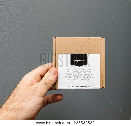 PARIS, FRANCE - JAN 23, 2018: Man holding against gray background a box of Amazon Basics Amazonbasics package containing USB-C to Ethernet Adapter