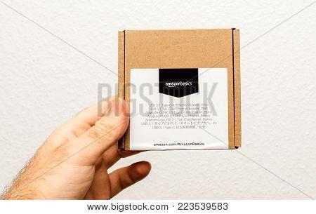 PARIS, FRANCE - JAN 23, 2018: Man holding against white background a box of Amazon Basics Amazonbasics package containing USB-C to Ethernet Adapter
