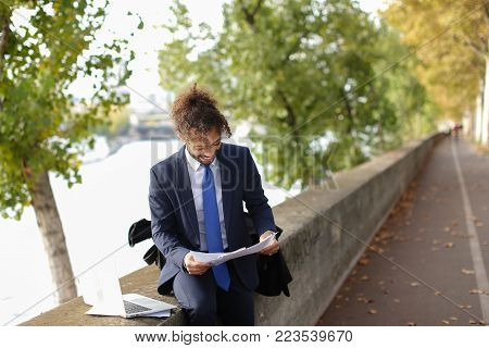Foreign student writing course work on Seine bank with laptop and papers. Arabian man dressed in suit with tie has long fleecy hair and charming smile. Concept working with documents on open air and modern devices.