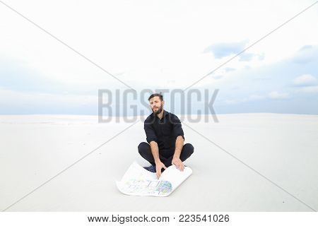 Clothier come to deserted place to plan own textile factory, fellow decide to rent land start business. Bearded guy sitting on sand unwrapping whatman paper looking around. Concept of exploring new territories, stylish outfits or young entrepreneur.