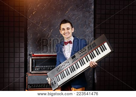 Musician with a synthesizer in the hands at a recording studio, piano keyboard