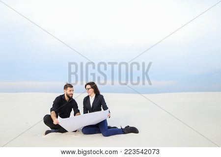 translators wife and husband move to alien city, married couple planning house at seaside. Young bearded fellow and fair-haired girl in glasses sitting on sand with  man and  paper. Concept of exploring new territories, plots of land for sale or modern cl