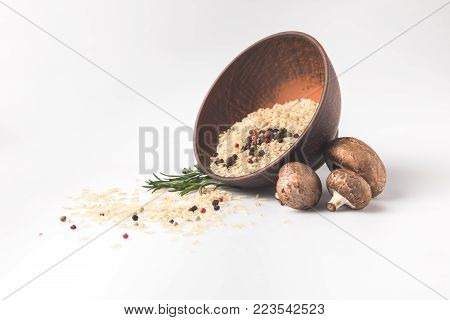 raw rice spilling out bowl on white surface with mushrooms