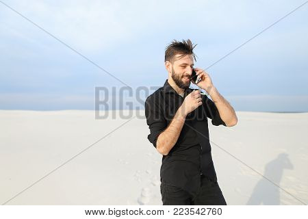 Husband speaking on smartphone with wife in business trip smoking, guy go for walk to seaside. Bearded fellow in black shirt smiling talking on phone standing among sands. Concept of innovative technologies, using gadgets for communication or modern mobil