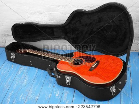 Musical instrument - Orange acoustic guitar in hard case on a blue wood, and white brock wall background.