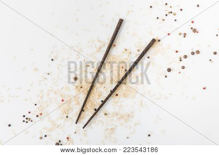 top view of raw rice and spices spilled on white surface with chopsticks