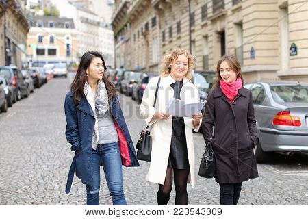 Chinese international student speaking with teacher outside in  . Concept of studying abroad and learning language. Young girls talking outside in coats.
