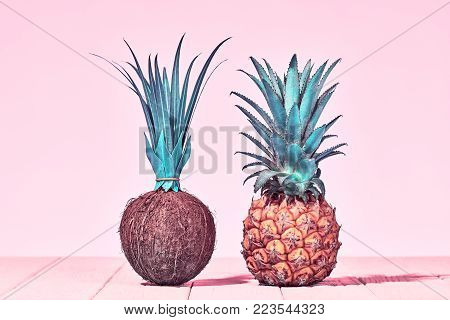 Pineapple and Coconut, Two Tropical Fruits. Vanilla Pastel Color. Creative Minimal. Hot Summer Vibes. Pink Beach background. Trendy Vintage Style.