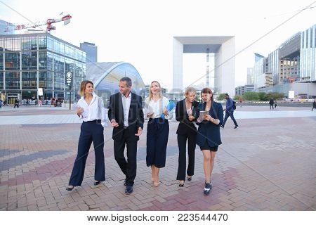 Members of business organization talking outside and smiling with document case and tablet in hands. Concept of walking biz team and resting outside. Group people dressed in suits and white shirts with close up faces.
