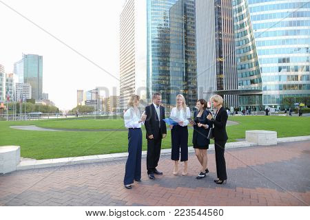 Employees of large corporation walking in slow motion with tablet, laptop, notebook and document case. Concept of team members having break outside. Successful people dressed in classic wear style.