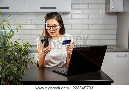 Young woman scared and holding a credit card and your smartphone.