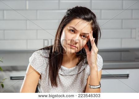 A young woman with a headache holding head. Headache, Women, Emotional Stress.