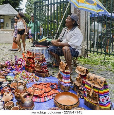 Belo Horizonte, Brazil - Dec 23, 2017: Indigenous Brazilian man selling arts and crafts at a street market in Belo Horizonte