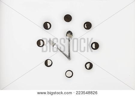 black cookies with white filling lies on a circle on a white background at the center of the spoon and fork