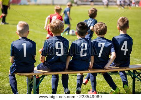 Young boys watching soccer competition from bench. Soccer players under 10 years old. Kids football club players in blue jersey. Kids group soccer players. European football tournament for children.