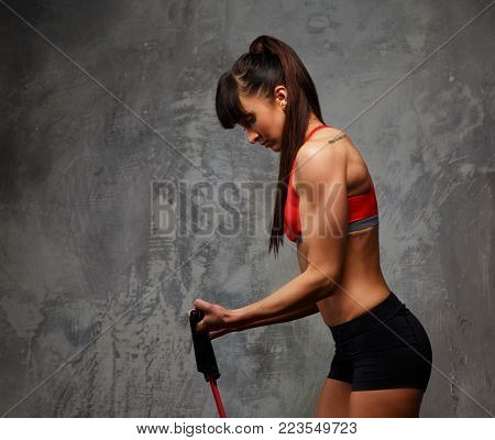 Fitness woman in sportswear doing exercises with expander on grey background. Side view